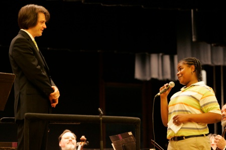 Wilkinsburg High ninth-grade percussionist Sarah Jackson presents PSO Conductor Daniel Meyer with parting gifts after his final concert in Wilkinsburg.